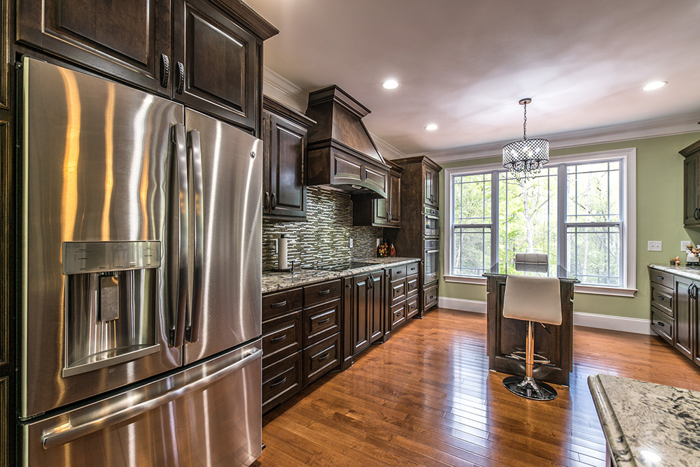 Delicatus White granite kitchen countertops with dark wood cabinets and stainless steel appliances