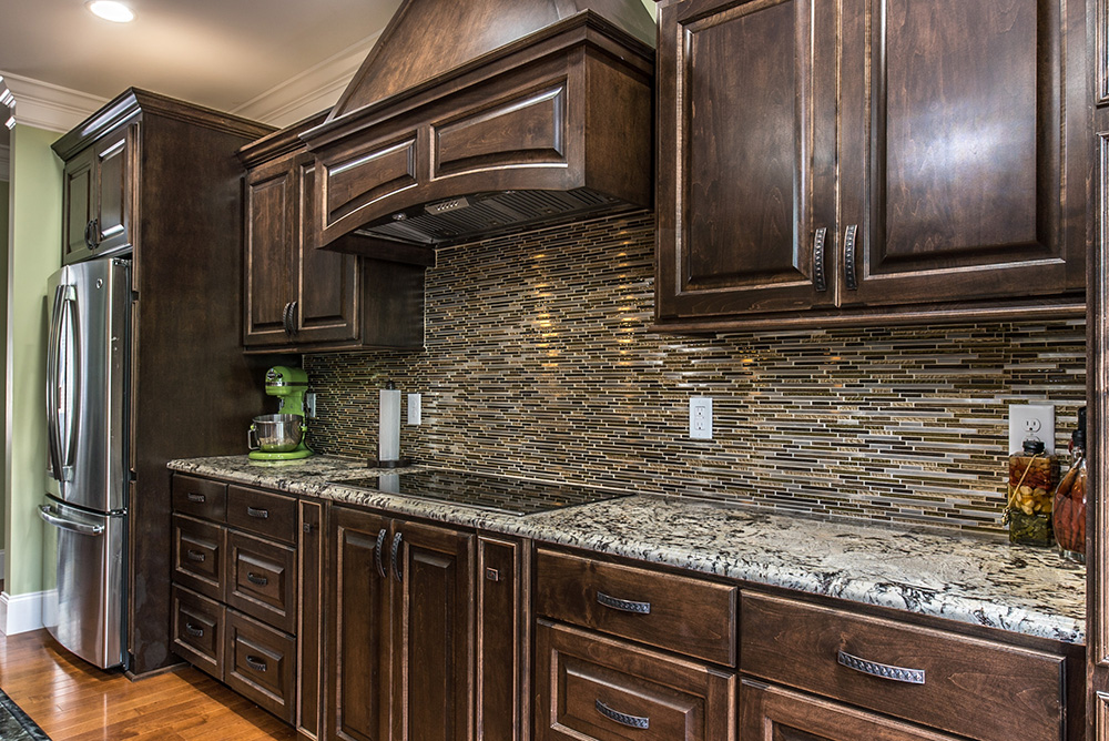 Food prep area utilizing Delicatus White granite and earth toned stacked glass tile backsplash
