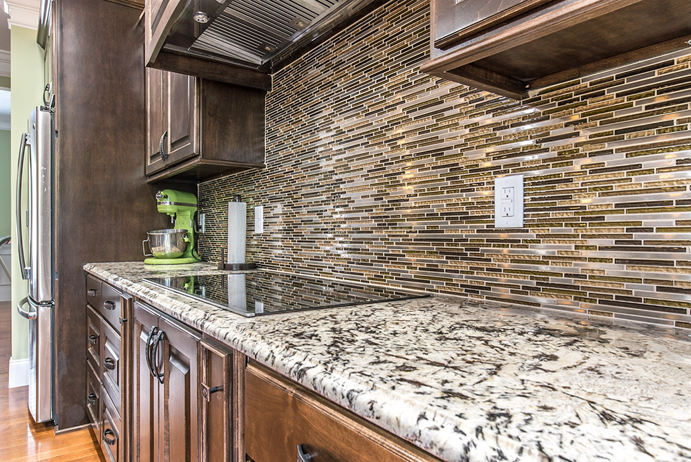 Delicatus White granite countertop matched with stacked glass tile backsplash and deep brown cabinetry