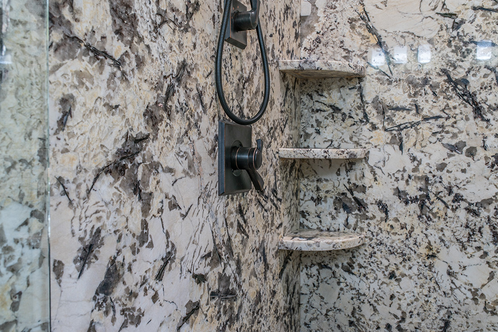 Delicatus White granite shower with corner shelves, bronze shower head, controls and glass door