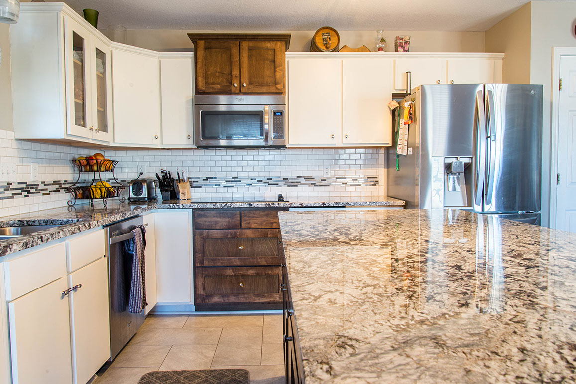Lennco Granite island countertop with corresponding countertops and subway and glass tile backsplash