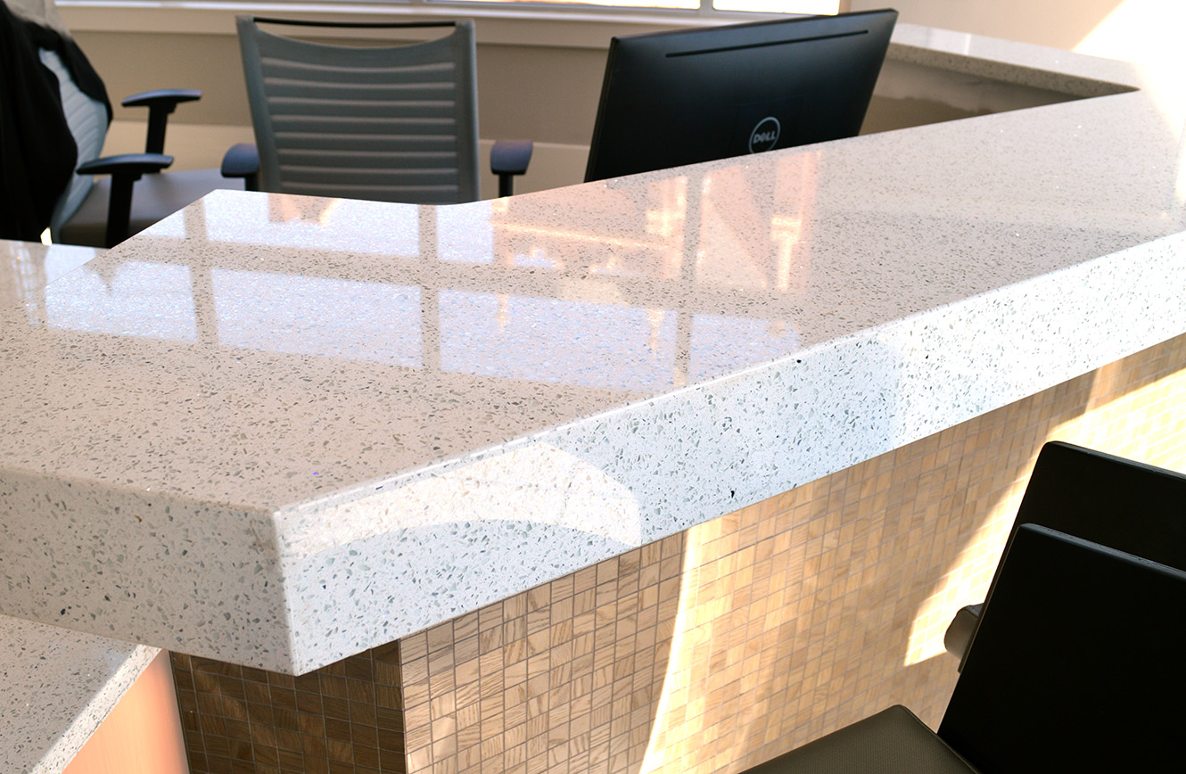 East Coast Granite installed Link Apartment's (Greenville, SC) receptionist desk with a Quartz countertop and tiled base.