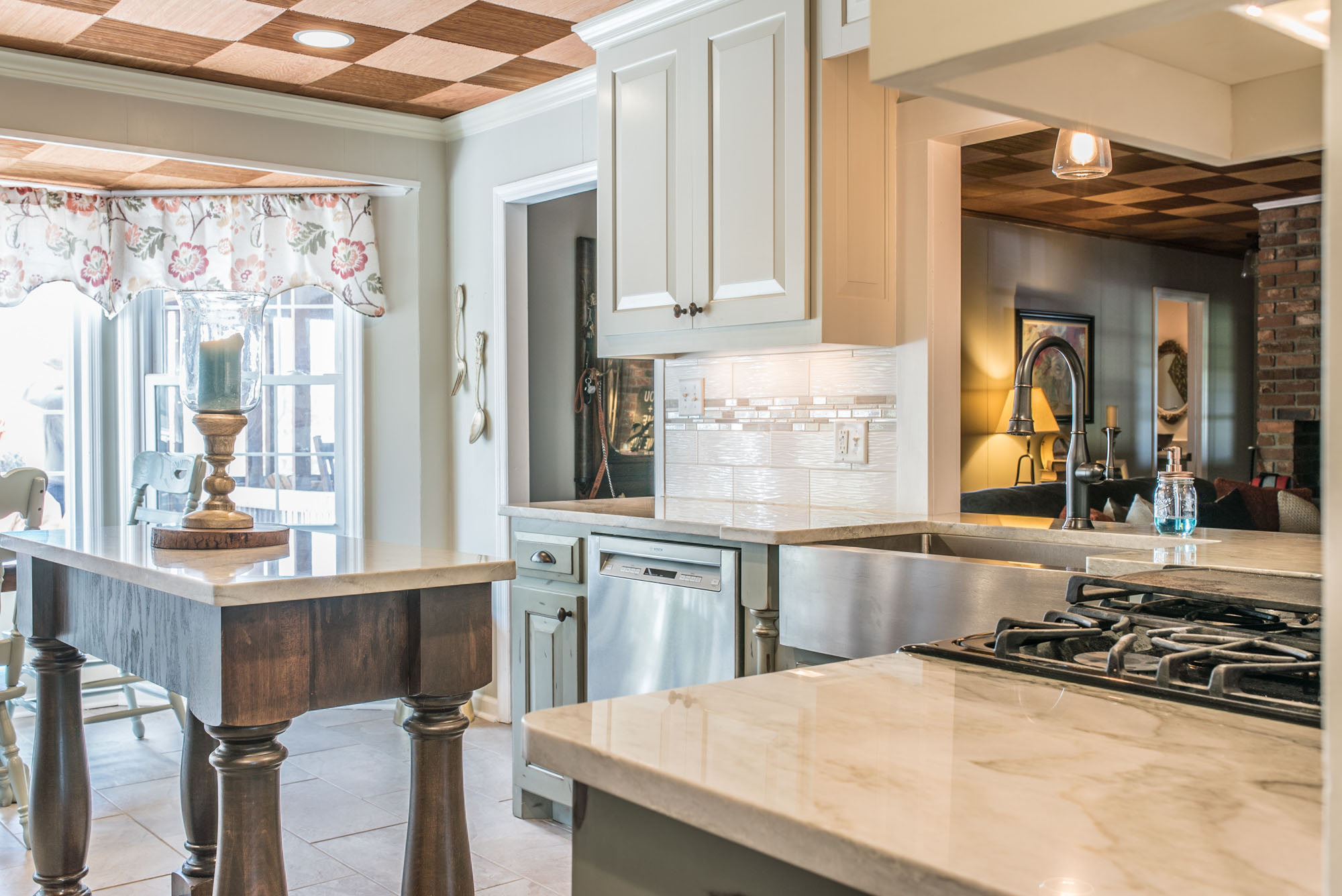 Sea Pearl Quartzite countertops matched with white stacked tile backsplash and stainless appliances