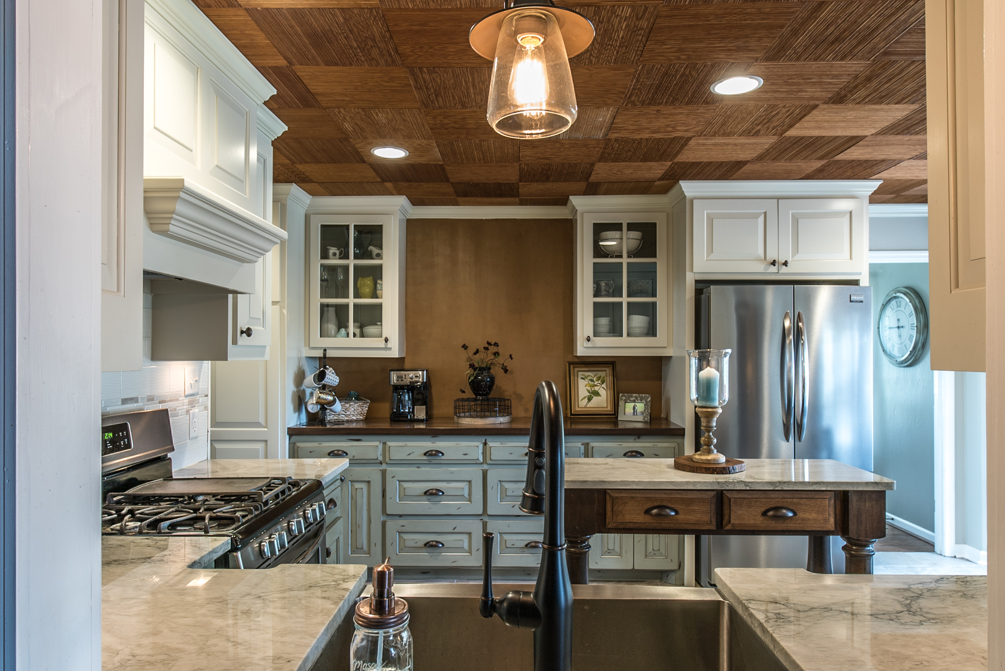 Sea Pearl Quartzite countertops contrasted by brown accent wall and ceiling tiles