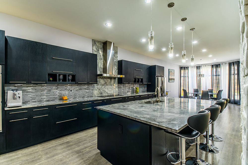 Large modern kitchen with Super White marble countertops, dark cabinets, stacked tile backsplash and stainless steel finishes