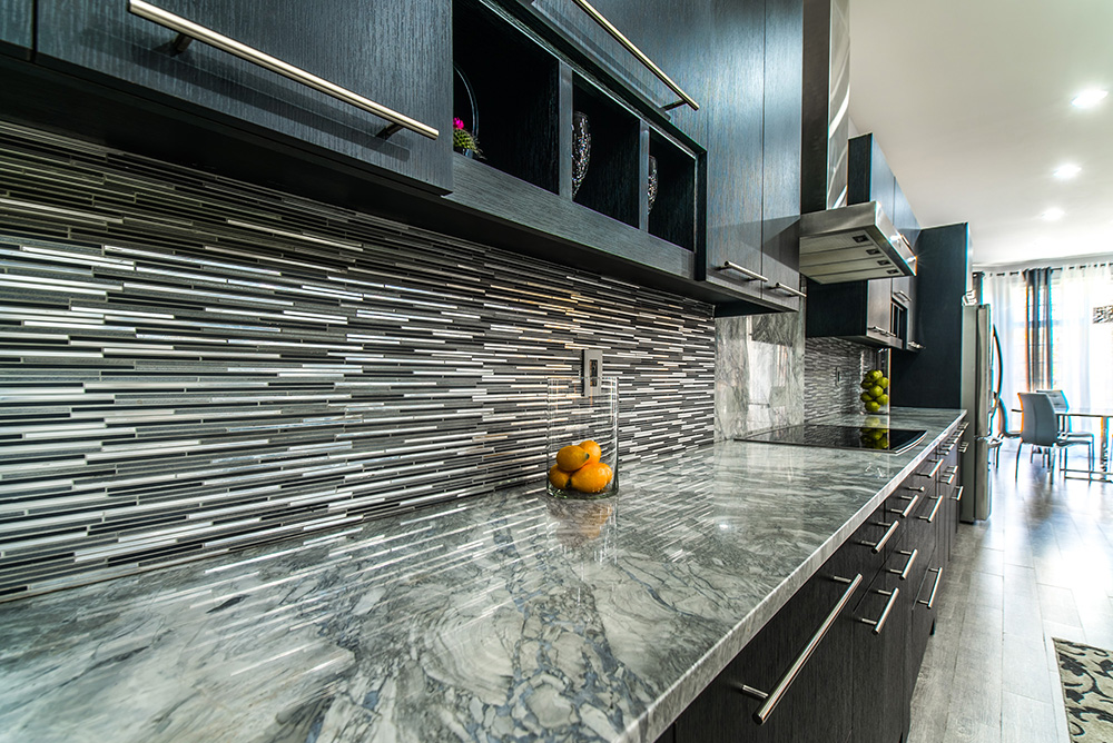 Super White marble countertop paired with dark wood cabinets, tile backsplash and stainless steel touches