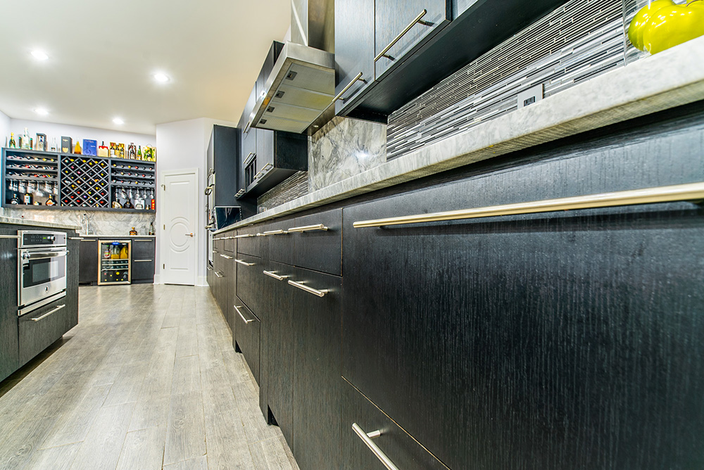 Dark wood cabinets and drawers topped with Super White Marble countertops and accented with stainless touches