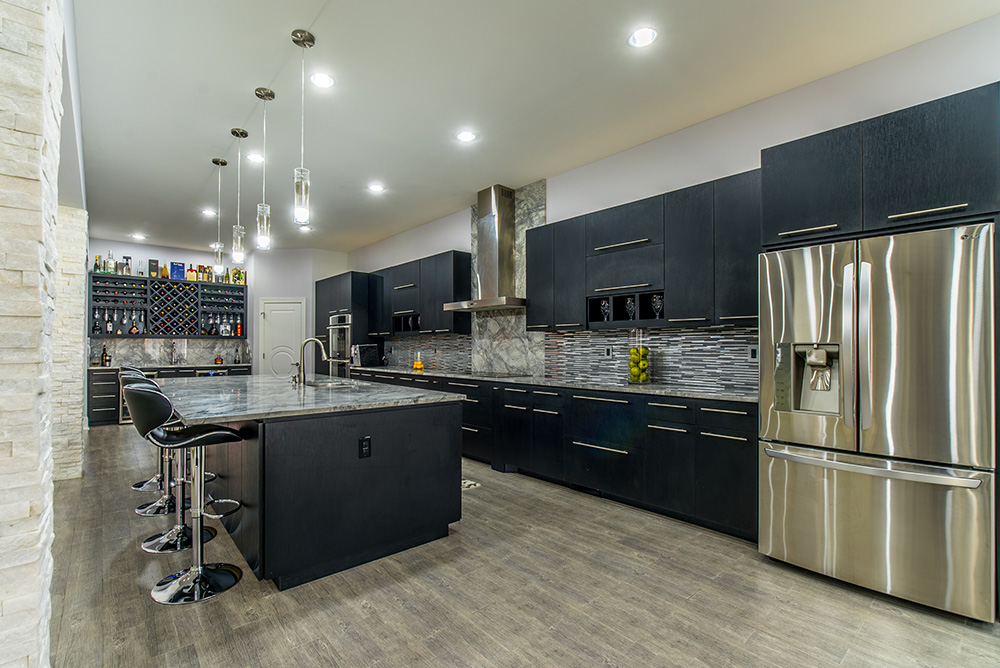 Spacious Kitchen With Black Cabinets, Stainless Appliances, Tile Backsplash  And Super White Marble Countertops