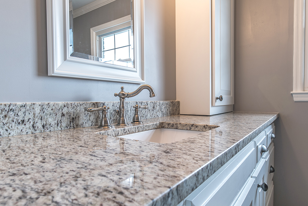Verona granite vanity paired with nickel finishes and white shaker cabinets